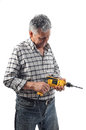 A worker holds an electric drill old man in studio Stock Photos