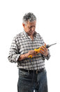 A worker holds an electric drill old man in studio Stock Photo