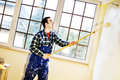 Worker house painter paints a wall in the background bright room Royalty Free Stock Images