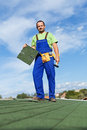Worker installing bitumen roof shingles standing on top of building Royalty Free Stock Photos