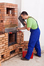 Worker installing door to a masonry heater Stock Images