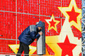 The worker installs the speakers on a red festive background with stars on the street in Volgograd