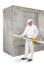 Worker with a lath in frotn of concrete wall Stock Image