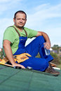 Worker laying bitumen roof shingles resting on top of building Stock Photo