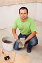 Worker laying ceramic floor tiles on concrete surface spreading the adhesive material Stock Photo