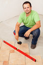 Worker laying ceramic floor tiles crouching and holding a rubber hammer Stock Image