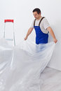 Worker laying down thin protective foil before painting nylon Royalty Free Stock Photo