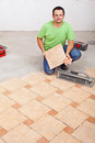 Worker laying floor tiles on concrete surface in a new building Stock Images
