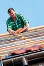 Worker laying tiles on roof Stock Photo