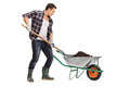 Worker loading dirt into a wheelbarrow young with shovel isolated on white background Stock Image