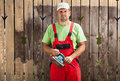 Worker man scraping old paint from fence with electric hand tool Royalty Free Stock Photo