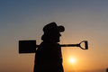 Worker man sunset silhouette day over shovel spade Royalty Free Stock Photo