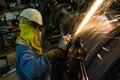 Worker metal grinding machine repair weld at steel roll