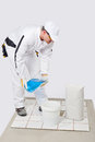 Worker mix tile adhesive bucket of water Stock Photo