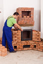 Worker mounting door to a masonry heater Stock Image