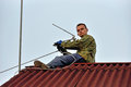 A worker mounts a individual uhf television antenna on the roof of the country house Stock Photography