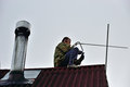 A worker mounts a individual uhf television antenna on the roof of the country house Stock Photo