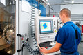 Worker operating CNC machine center Royalty Free Stock Photos