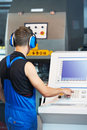 Worker operating cnc punch press Royalty Free Stock Images