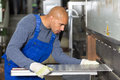 Worker operating machine for bending sheet metal Royalty Free Stock Photo