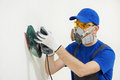 Worker with orbital sander at wall filling Royalty Free Stock Photo