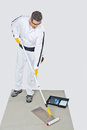 Worker with paint roller primed primer concrete floor for waterproofing Royalty Free Stock Photo