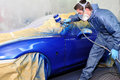 Worker painting a blue  car. Royalty Free Stock Photo