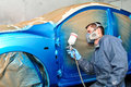 Worker painting blue car. Stock Photos