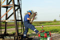 Worker with pipe wrench on pipeline oilfield Royalty Free Stock Images