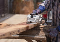 Worker planing a wood with a electric plane Royalty Free Stock Photo