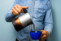Worker pouring coffee from moka pot blue collar Royalty Free Stock Images