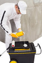 Worker pouring a primer in a paint tray yellol bottle Royalty Free Stock Image