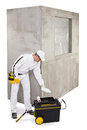 Worker pouring a primer to prepare cement wall Stock Photo