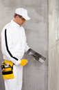 Worker preparing a putty cement to fix corner of wall Royalty Free Stock Image