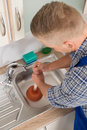 Worker pressing plunger in sink high angle view of steel kitchen Stock Image