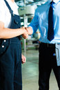 Worker and production manager in a factory or owner ceo or controller shake hands Royalty Free Stock Photos