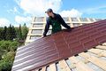 Worker puts the metal tiles on the roof Royalty Free Stock Photo