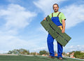 Worker putting bitumen shingles on a roof standing top of building Stock Photography