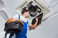 The worker repairing ceiling air conditioning unit Royalty Free Stock Photo