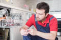 Worker repairing the dishwasher in the kitchen Royalty Free Stock Photo