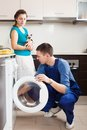 Worker repairing washing machine woman watching as Royalty Free Stock Images