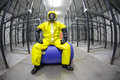 Worker in safety protective uniform sitting on blue barrel portrait fish eye lens Stock Photography