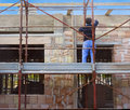 Worker on scaffold building masonry clay blocks Royalty Free Stock Photos