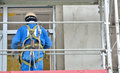 Worker on a scaffold construction in protective equipment Royalty Free Stock Image