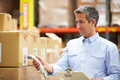 Worker scanning package in warehouse looking at boxes Stock Image