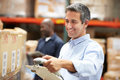 Worker scanning package in warehouse smiling Stock Image