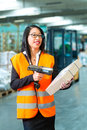 Worker scans package in warehouse of forwarding logistics female or shipper with protective vest and scanner bar code he standing Stock Images