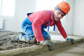 Worker screeding indoor cement floor with screed Royalty Free Stock Photo