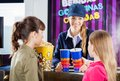 Worker selling snacks to girls at concession female drinks and popcorn cinema counter Stock Photo