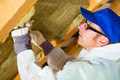 Worker setting thermal insulating material in overall is with gloves in the roof Stock Image